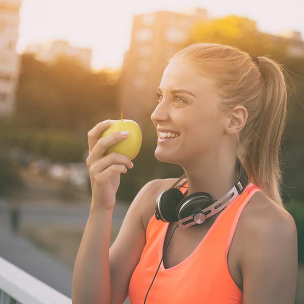 Egy nő almát eszik, háttérben egy város