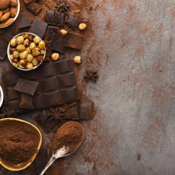 Dark broken chocolate pieces on dark background, cocoa powder and various nuts in bowls closeup. Sweet wallpaper, confectionery shop advertising and cooking ingredients concept, topv iew, copy space